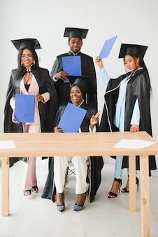 Bildung, abschluss und menschenkonzept - gruppe glücklicher internationaler studenten.
