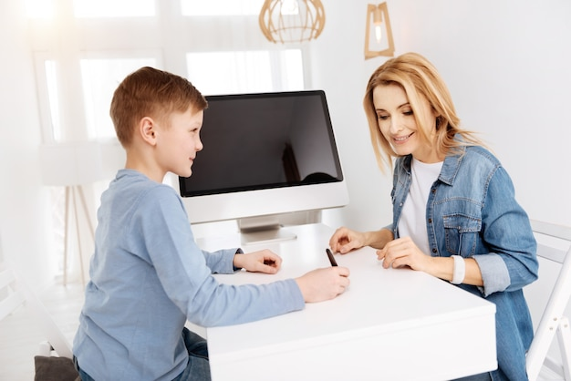 Bildung der zukunft. netter positiver glücklicher junge, der am tisch sitzt und auf einem digitalen bildschirm schreibt, während er mit seiner mutter studiert