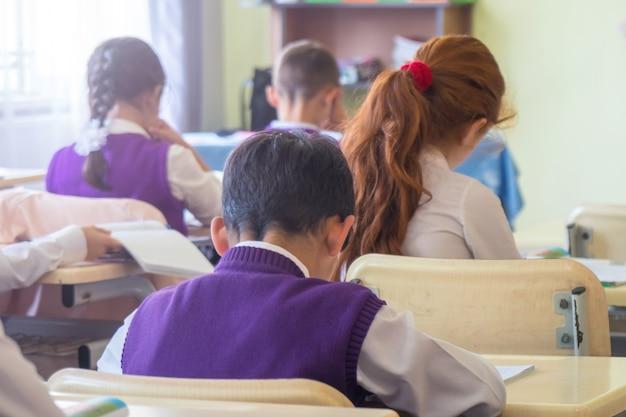 Bildung grundschule gruppe von schulkindern sitzen und hören lehrer im klassenzimmer