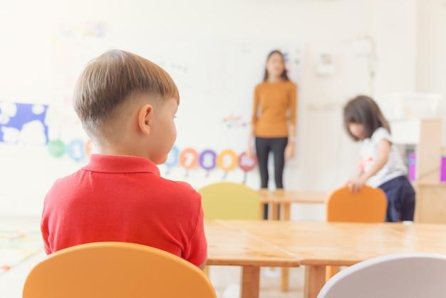 Bildung, grundschule, lernen und menschen konzept - gruppe von schulkindern mit lehrer sitzen im klassenzimmer. vintage effekt stil bilder.