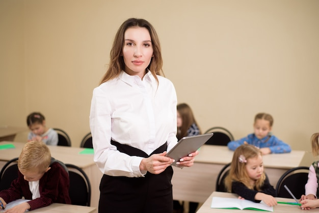 Bildung, grundschule, lernen und menschenkonzept. lehrer und schüler im hintergrund.