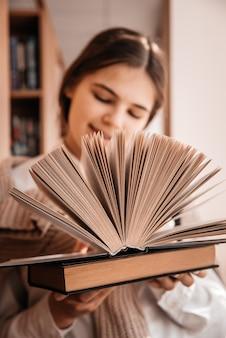 Bildung, high school, universität, lernen und menschenkonzept - lächelndes studentenmädchen, das buch in der bibliothek liest