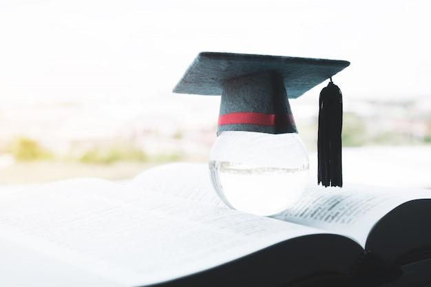 Bildung in globalem, abschlusskappe auf spitzenglaskugel auf lehrbuch