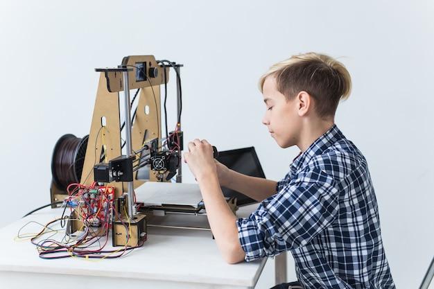 Bildung, kinder, technologiekonzept - jugendlich junge druckt auf 3d-drucker.