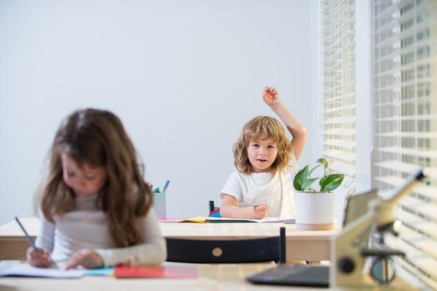 Bildung, lernen und menschen-konzept. kleines studentenmädchen mit buchschreiben-schultest. zurück zur schule. glückliches süßes kind sitzt drinnen an einem schreibtisch.