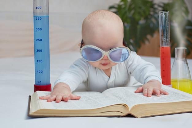 Bildung und heimtraining. süßes baby liest ein buch über medizin, wissenschaft, chemische experimente. horizontales bild