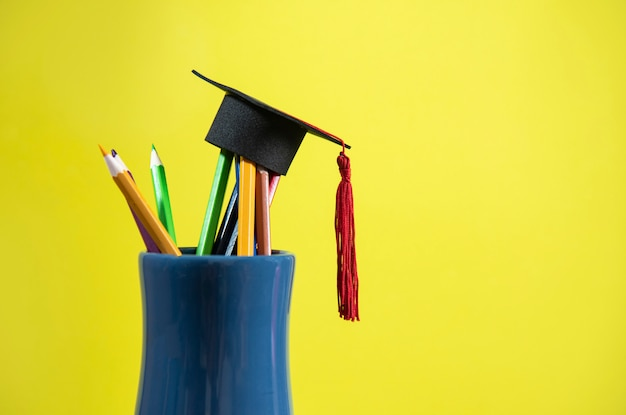 Bildung und zurück zu schulkonzept mit staffelungskappe auf bleistiften färben in einem bleistiftkasten