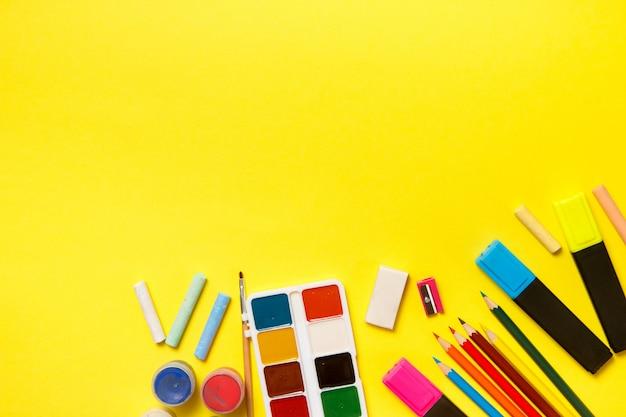 Bildung und zurück zum schulkonzept. schulbedarf für das zeichnen auf einen gelben hintergrund. draufsicht, flach zu legen.