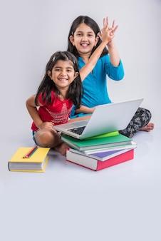 Bildung zu hause konzept - 2 süße kleine verspielte indische oder asiatische mädchen studieren oder hausaufgaben auf dem laptop über einem stapel bücher machen, während sie zu hause auf dem boden sitzen. auf weißem hintergrund isoliert