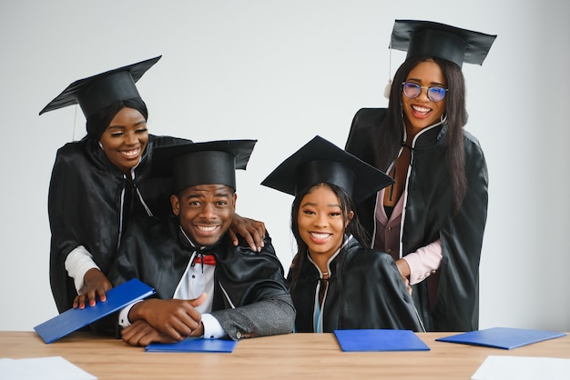 Bildungs-, abschluss- und menschenkonzept - gruppe glücklicher internationaler doktoranden in mörtelbrettern und bachelor-kleidern mit diplomen