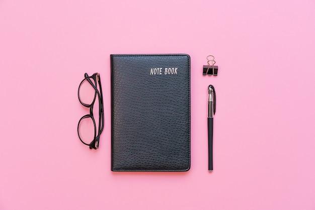 Bildungs- oder geschäftskonzept draufsicht auf schwarzes notizbuch mit moderner brille und schwarzem stift isoliert ...