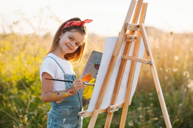 Bildungs-, schul-, kunst- und malkonzept - kleines studentenmädchen, das bild malt