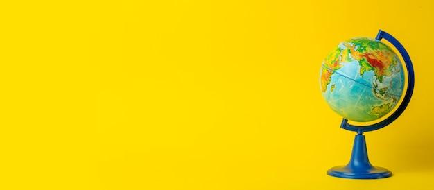 Bildungs- und globalismuskonzept. kugel auf einem offenen buch auf einer tabelle in einer hochschulklasse auf einem gelben hintergrund