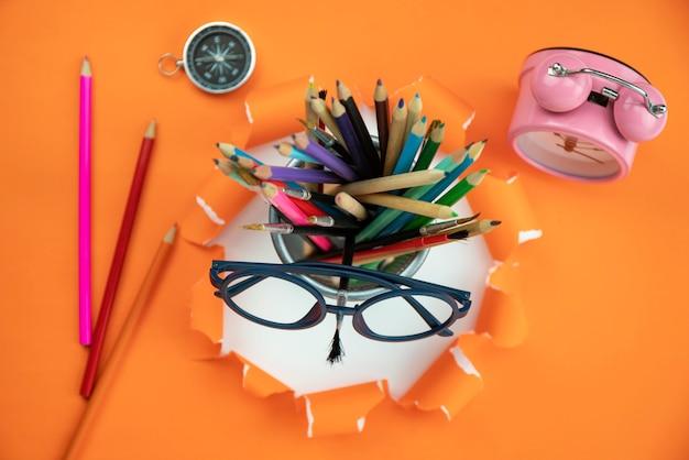 Bildungsgegenstände auf orange zerrissenem offenem papier