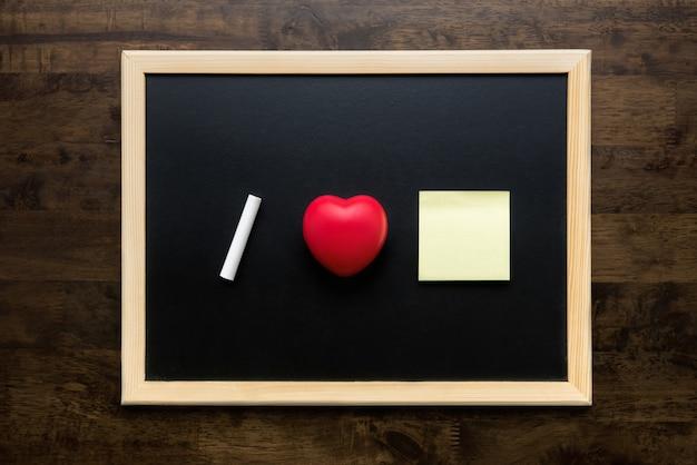 Bildungskonzept des liebesherzsymbols und der weißen kreide auf einer tafel draufsicht