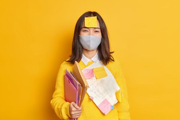 Bildungskonzept für soziale distanzierung und selbstisolation. student der asiatischen universität trägt eine schützende gesichtsmaske, während coronavirus ordner trägt und memo-aufkleber die abschlussprüfung von zu hause aus vorbereiten