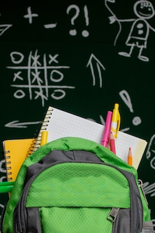 Bildungskonzept - grüner rucksack, notizbücher und schulmaterial auf dem hintergrund der tafel