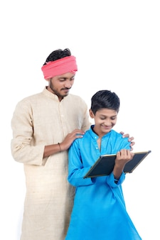 Bildungskonzept: indischer bauer mit seinem schuljungen auf weißem hintergrund.