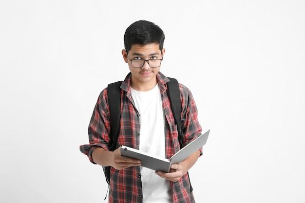 Bildungskonzept: indischer college-student, der tasche und lesebuch auf weißem hintergrund hält