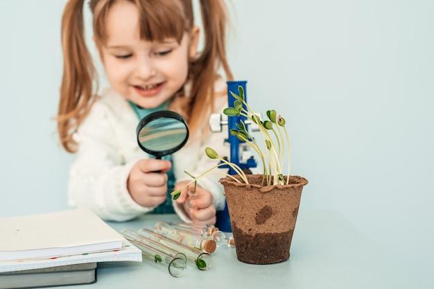 Bildungskonzept. little baby girl blick auf die mikroskope im labor.