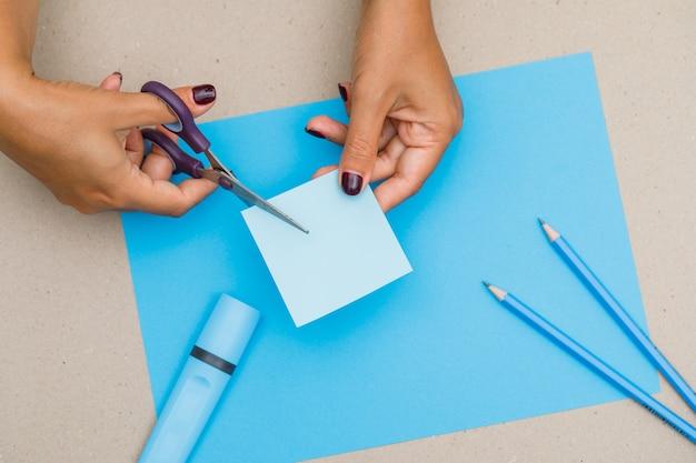 Bildungskonzept mit schulmaterial auf papier, flach gelegt. frau schneidet haftnotiz.