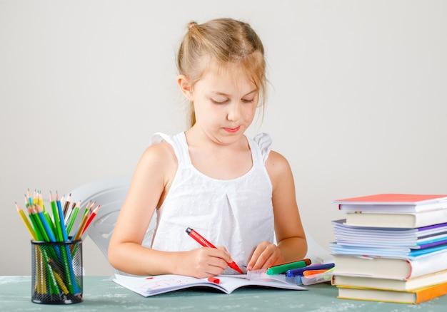Bildungskonzept mit seitenansicht des schulbedarfs. kleines mädchen, das auf heft zeichnet.