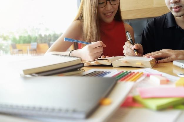 Bildungskonzept studentisches studium und brainstorming campus konzept. nahaufnahme von studenten diskutieren ihr thema auf bücher oder lehrbücher. selektiver fokus