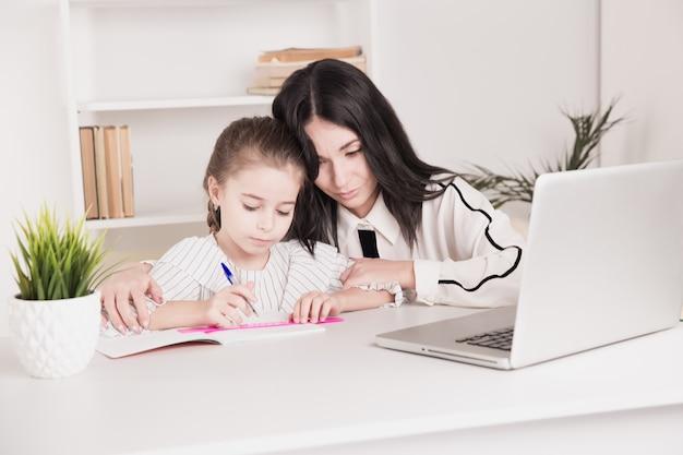 Bildungskonzept zu hause. tutor und mädchen, die zusammen hausaufgaben machen.