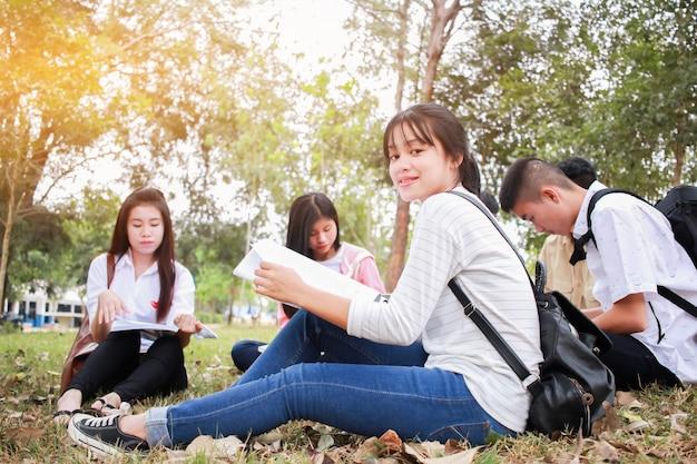 Bildungslernstudie im freien konzept: die überzeugten asiatischen studentengruppen, die sitzen, lasen buch