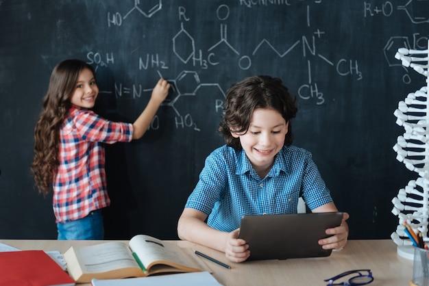 Bildungsprozess genießen. brainy begabte intelligente teenager, die in der schule sitzen und den chemieunterricht genießen, während sie sich notizen an die tafel machen und das tablet verwenden