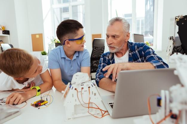 Bildungssystem. angenehmer lehrer im alter, der mit seinen schülern spricht und ihnen roboter erklärt
