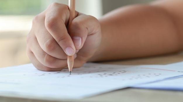 Bildungstest im universitäts- oder gymnasialkonzept hands student hält bleistift zum testen von prüfungen auf antwort