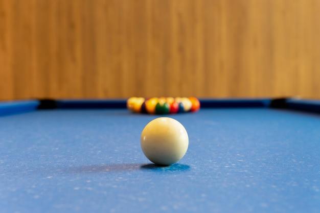 Billard-pool-spiel. weißer ball auf stelle mit satzfarbball im hintergrund auf blauer tabelle.