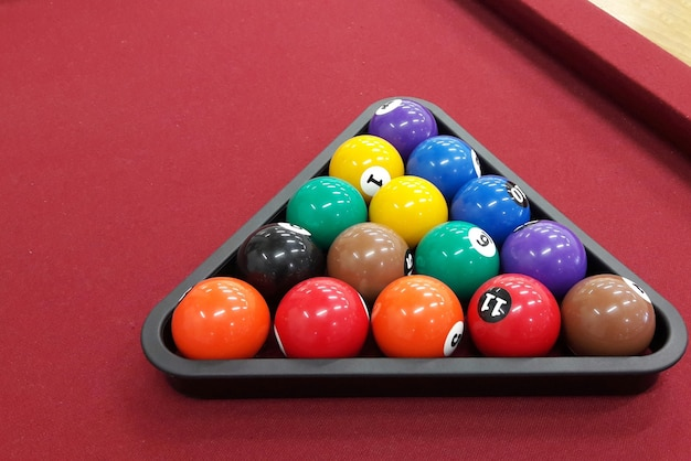 Billardkugeln im dreieck auf rotem tisch angeordnet
