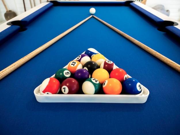 Billardkugeln im weißen dreieck und queue auf dem blauen tisch. billardsportkonzept. pool-billard-spiel.