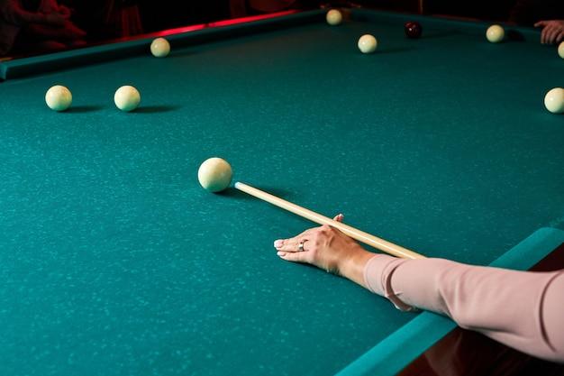 Billardspiel die hand der frau mit einem billard-queue zielt auf eine billardkugel. sportspiel billard
