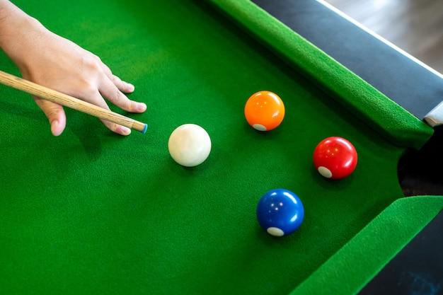 Billardtisch, den er einen weißen ball des snookers zum roten ball auf dem tisch spielt