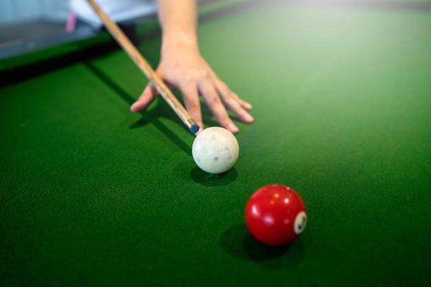 Billardtisch, den er einen weißen ball des snookers zum roten ball auf dem tisch spielt.