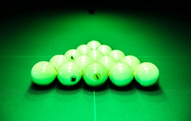 Billardtisch mit einem dreieck aus weißen spielkugeln darauf. freizeitkonzept für sport und indoor-spiele.