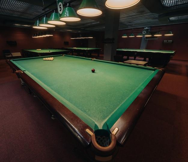 Billardtisch mit grüner oberfläche und kugeln im billardclub.pool-spiel.