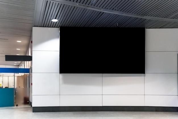 Billboard oder werbeplakat im flughafen für den hintergrund des werbekonzepts. ein großer schwarzer bildschirm an einer weißen wand im wartezimmer bahnhof, busbahnhof. plakat an einem öffentlichen ort