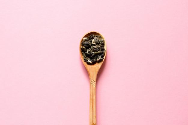 Biluochun. grüner tee des chinesischen blattes in einem löffel auf einem rosa hintergrund.
