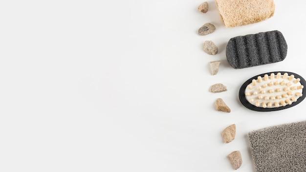 Bimsstein; massagebürste; luffa und spa-steine in reihe auf weißem hintergrund angeordnet