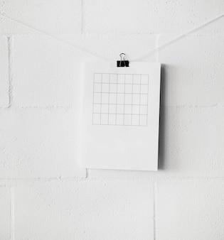 Bin leerer tisch über papierbefestigung an einer schnur mit büroklammer gegen weiße wand