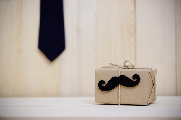 Bindung, geschenkbox, papierschnurrbart auf hölzernem hintergrund mit kopienraum. alles gute zum vatertag.