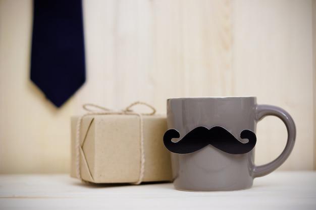 Bindung, geschenkbox, papierschnurrbart, kaffeetasse auf hölzernem hintergrund mit kopienraum. alles gute zum vatertag.