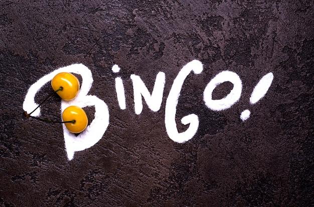 Bingo-typografie mit zuckerpulver und zwei gelben wildkirschen