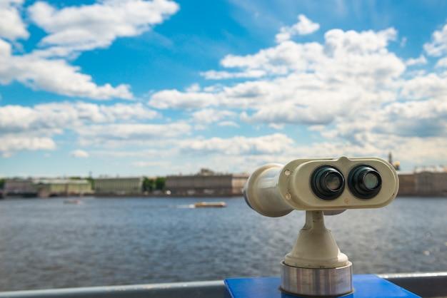 Binokular auf aussichtsplattform, selektiver fokus, blick auf stadt und himmel mit wolken.