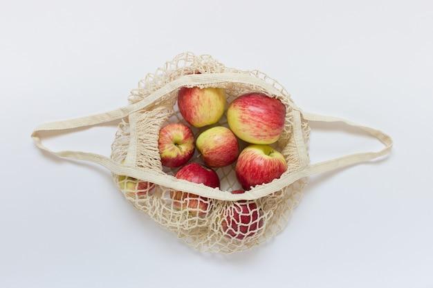 Bio-äpfel in einem geöffneten string-beutel auf weißem beutel.