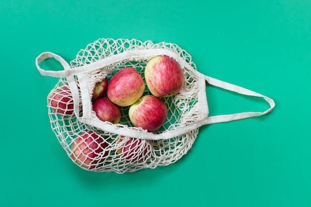Bio-äpfel in einer geöffneten, biologisch abbaubaren, umweltfreundlichen saitentasche auf grünem hintergrund.